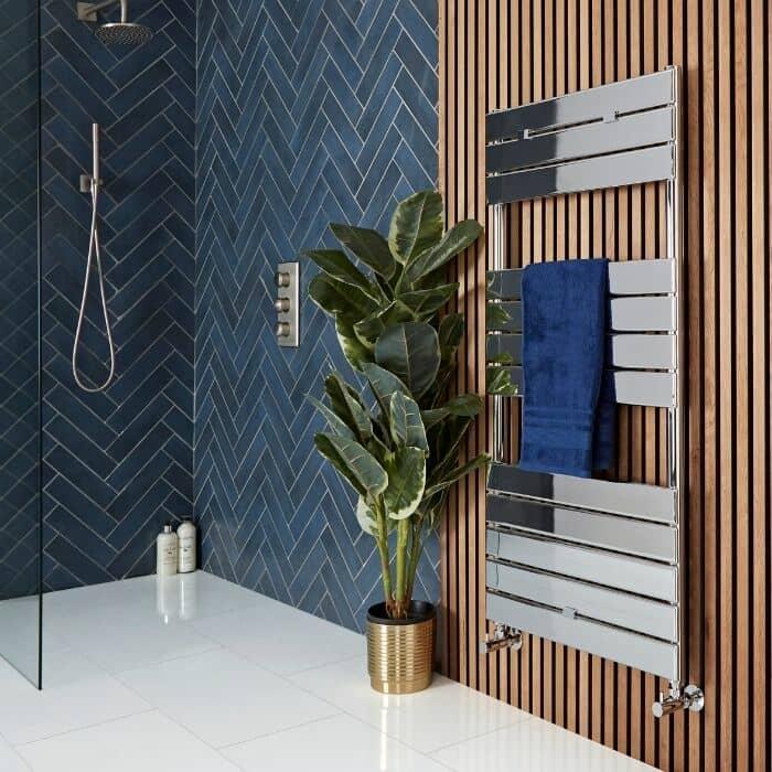 chrome heated towel rail on a wooden bathroom wall