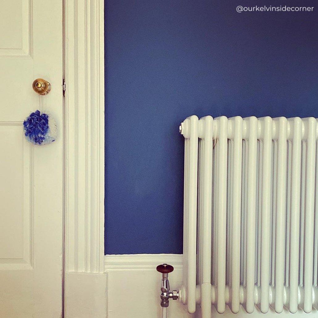 white column radiator on a classic blue wall