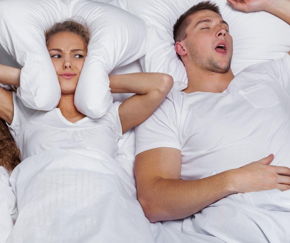 man snoring next to partner