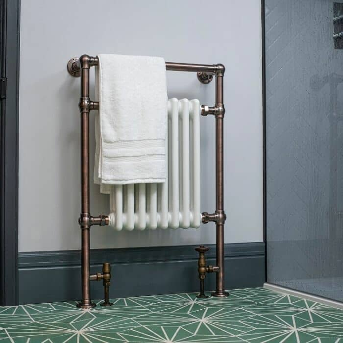 bronze heated towel rail with white columns in a blue bathroom