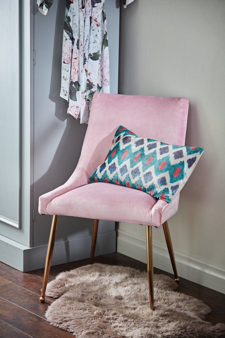 pink velvet chair in a bedroom