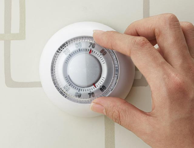 woman's hand turning off a thermostat
