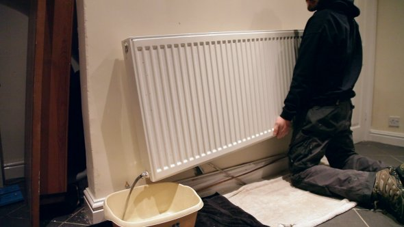 Man pouring water from a radiator into a washing up bowl