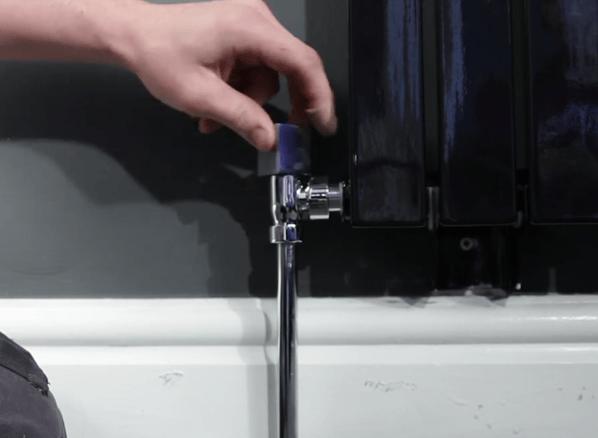 A hand turning a chrome radiator valve on a designer radiator