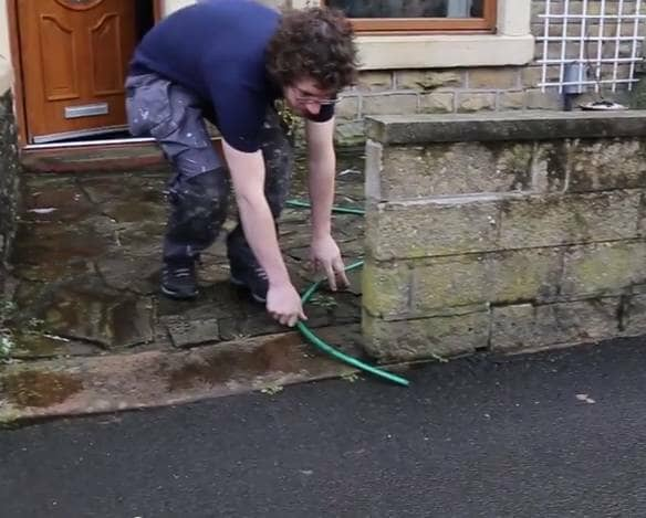 A plumber placing a hosepipe outside the front of a house and garden