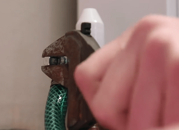 Plumber using a spanner to turn the valve and drain water from a radiator