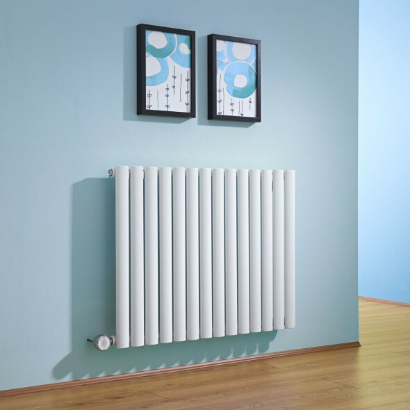 White electric designer radiator hung on a blue wall with two pictures above the radiator