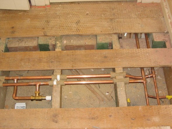 Pipework exposed under some floorboards