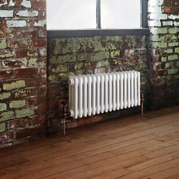white column radiator under a window on a brick wall