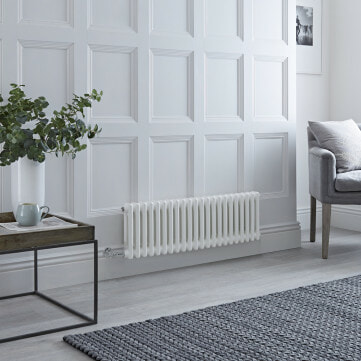A white Milano Windsor horizontal electric radiator on a white wall next to a grey chair and wooden table.