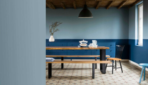 A dining room painted blue with a long dining table and benches