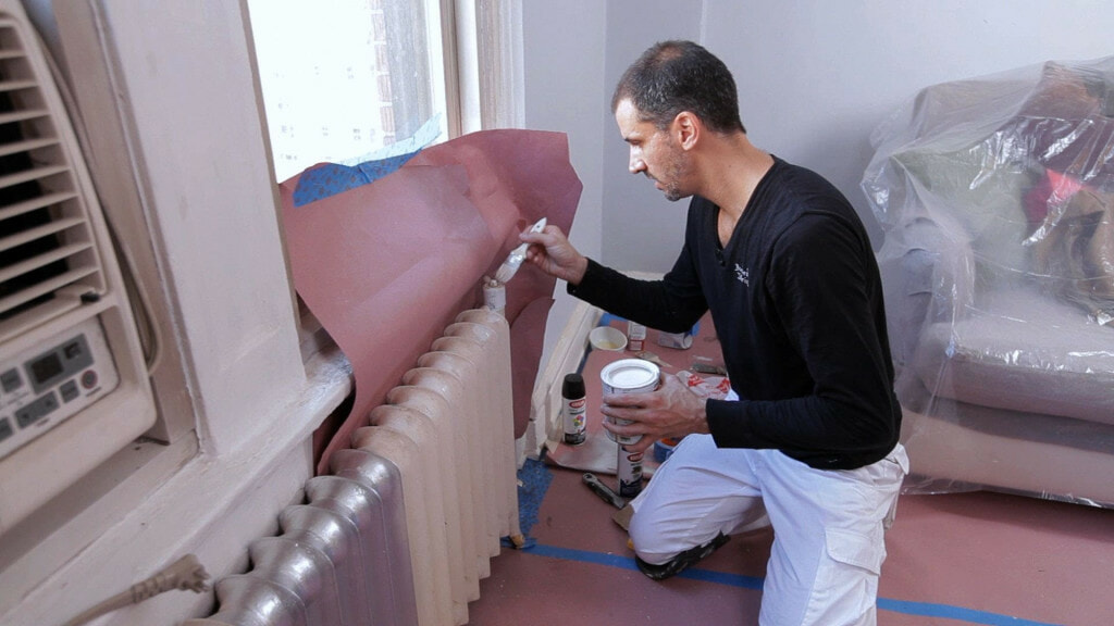 A man applying primer to a radiator before painting it in full