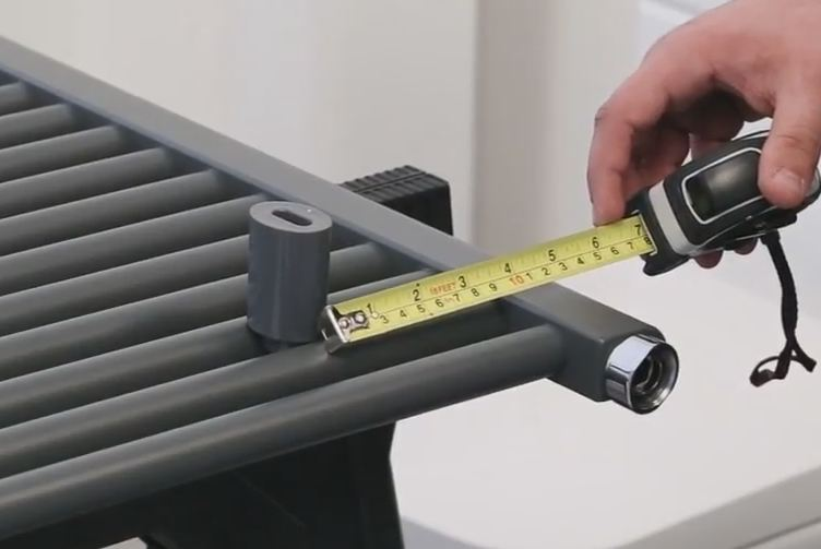 man measuring the distance between the centre of a bracket and the edge of a heated towel rail