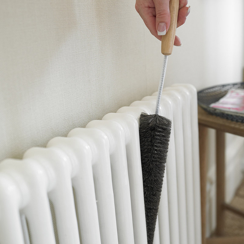person cleaning a radiator with a specialist radiator brush