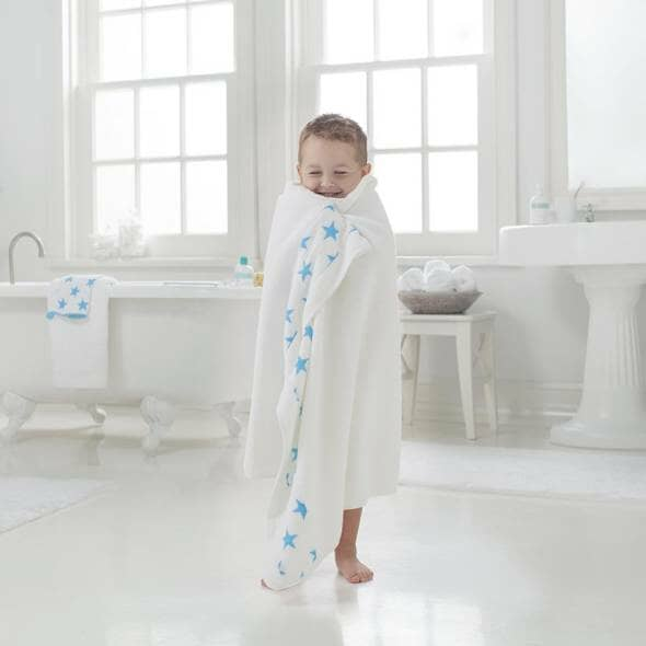 kid in white and blue towel getting out of the bath smiling