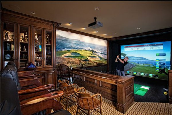 Man playing golf indoors on a golf simulator in his man cave