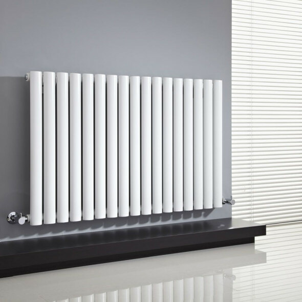 White designer radiator on a grey wall with a blind
