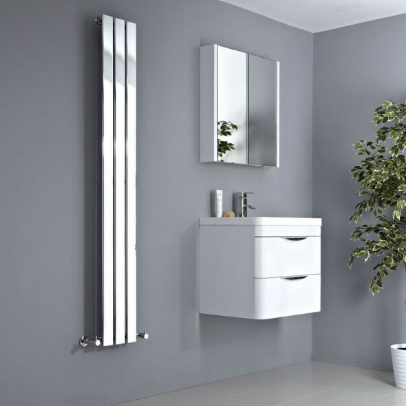 mirrored vertical radiator in a bathroom next to a sink