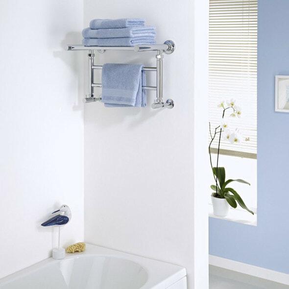 Milano Pendle Chrome Heated Towel Rail with a shelf above a bath in a bathroom