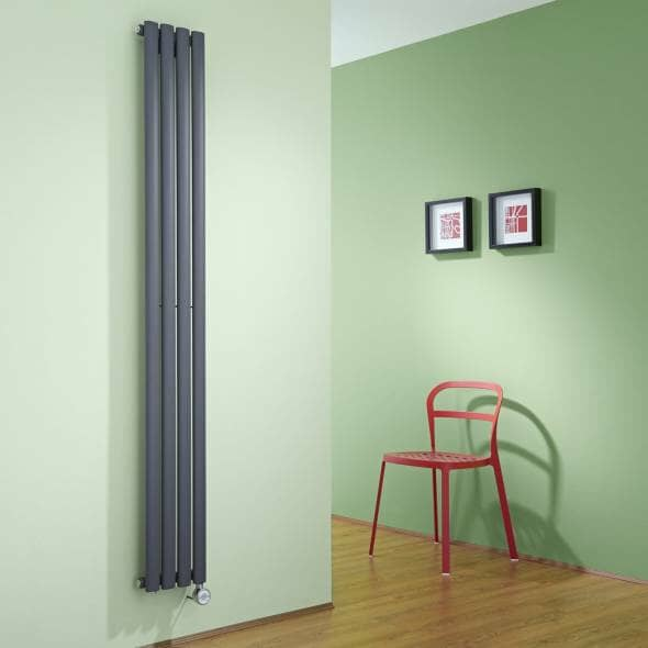 Tall vertical Grey electric radiator on a green wall