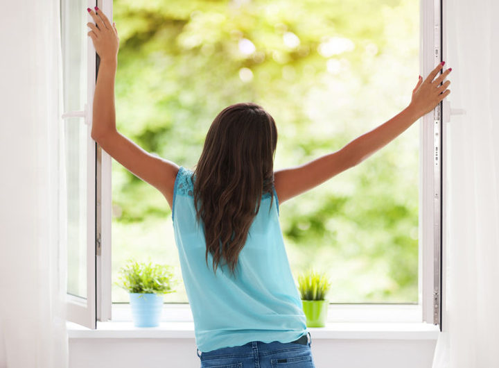 A dark haired woman opening a double glazed double window