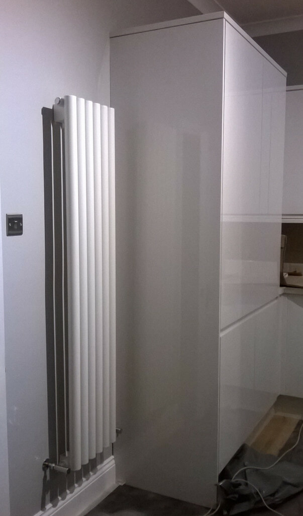Milano Java white round tubed vertical designer radiator on a kitchen wall