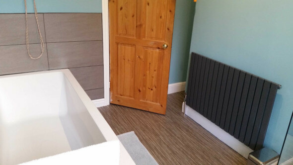 The after picture of a bathroom with a new radiator, flooring and bath suite