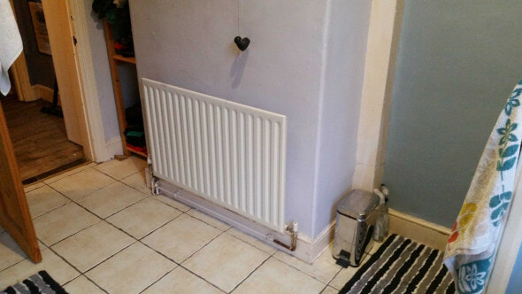 The picture of a bathroom before a new radiator and new bath were put in