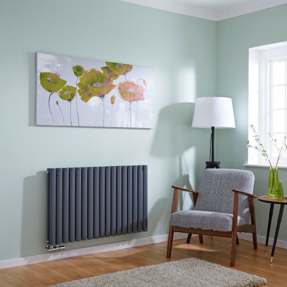 Grey Milano Aruba Flow middle connection designer radiator on a green wall in a sitting room next to a chair and a picture of some flowers