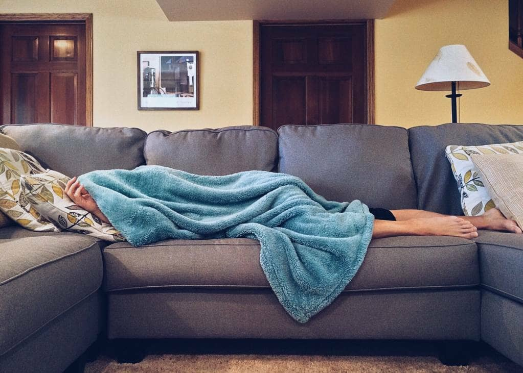 A person lying on a sofa under a blanket