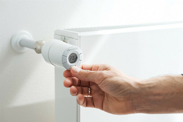 a hand turning a devolo home control radiator thermostat
