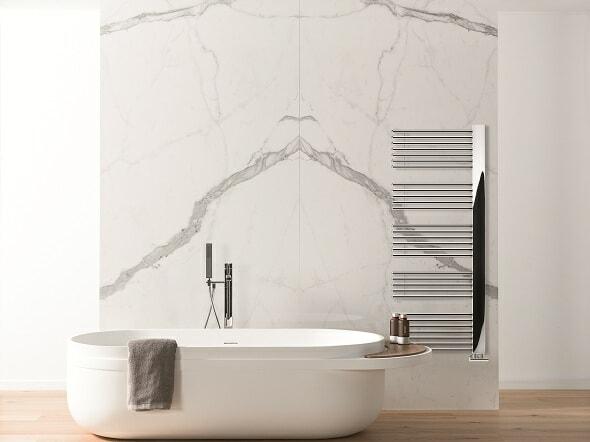The Lazzarini Way Grado heated towel rail on a marble wall in a bathroom with a freestanding bathtub