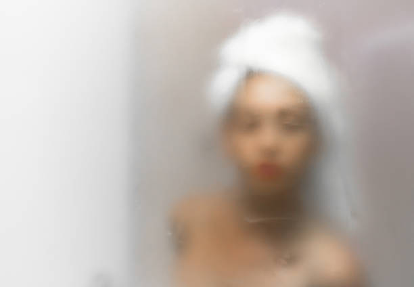a woman wearing a towel on her head in a steamy bathroom