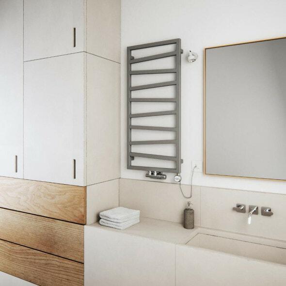 A silver Terma ZigZag dual fuel towel radiator in a bathroom next to a mirror