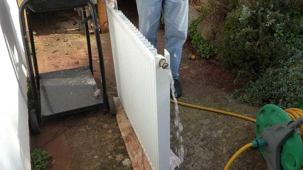 a radiator being flushed with a garden hose to clean out the inside of the radiator