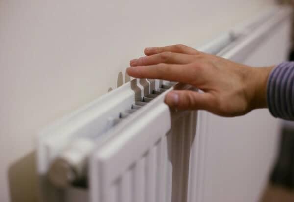 hand on radiator checking heat output.