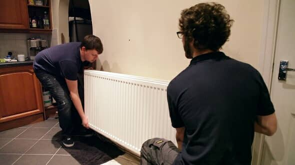 two men lifting a radiator from its mounting on a wall