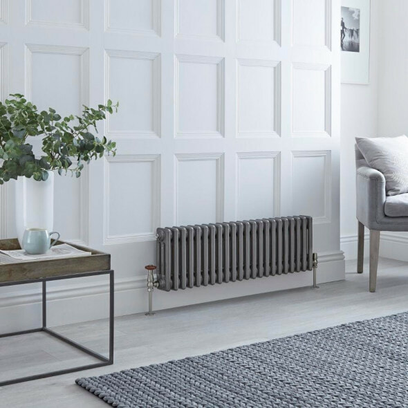 raw metal milano windsor cast iron style radiator on a white panelled wall in a sitting room