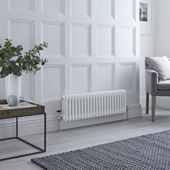 white radiator on white wall with grey furniture