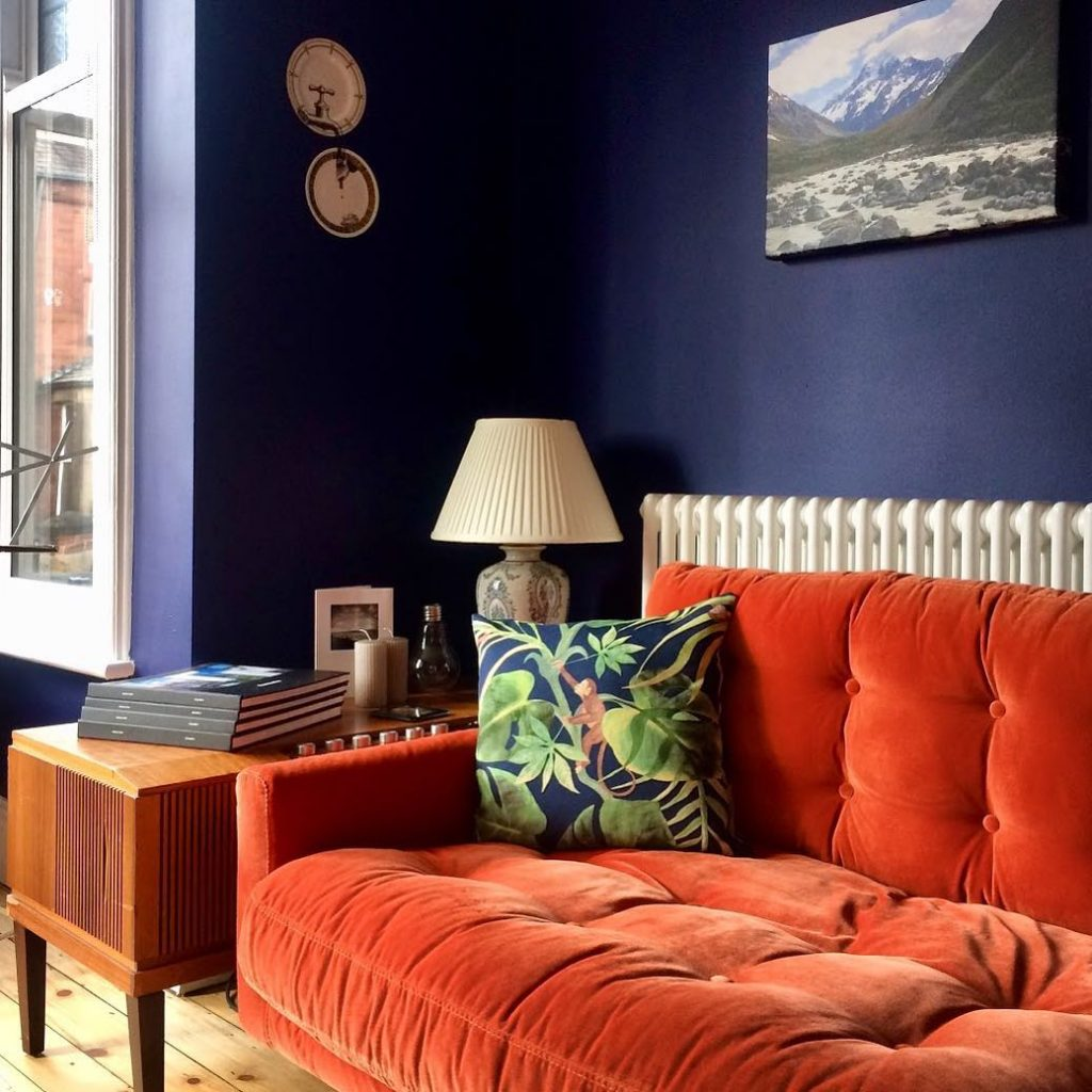 orange velvet sofa in a navy living room