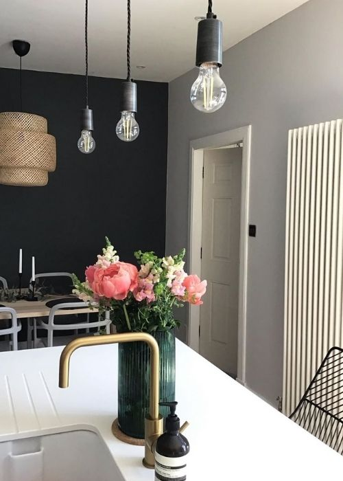 flowers on a kitchen island next to a vertical radiator