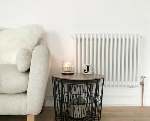 Milano Windsor column radiator next to a sofa.