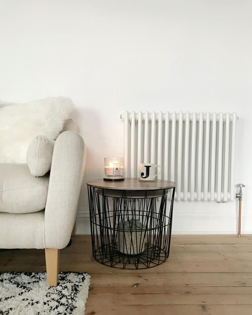 Milano Windsor column radiator next to a sofa.