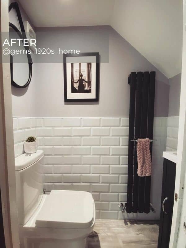 a modern vertical radiator in a small white bathroom