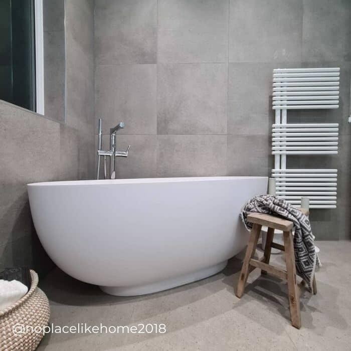 white ladder style heated towel rail in a grey bathroom