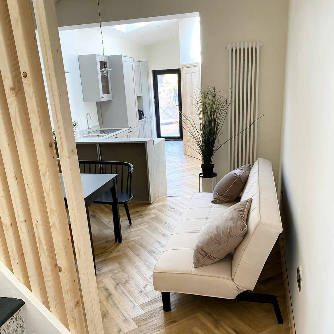 white vertical radiator in a neutral living room