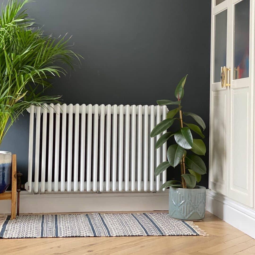 white column radiator on a navy wall