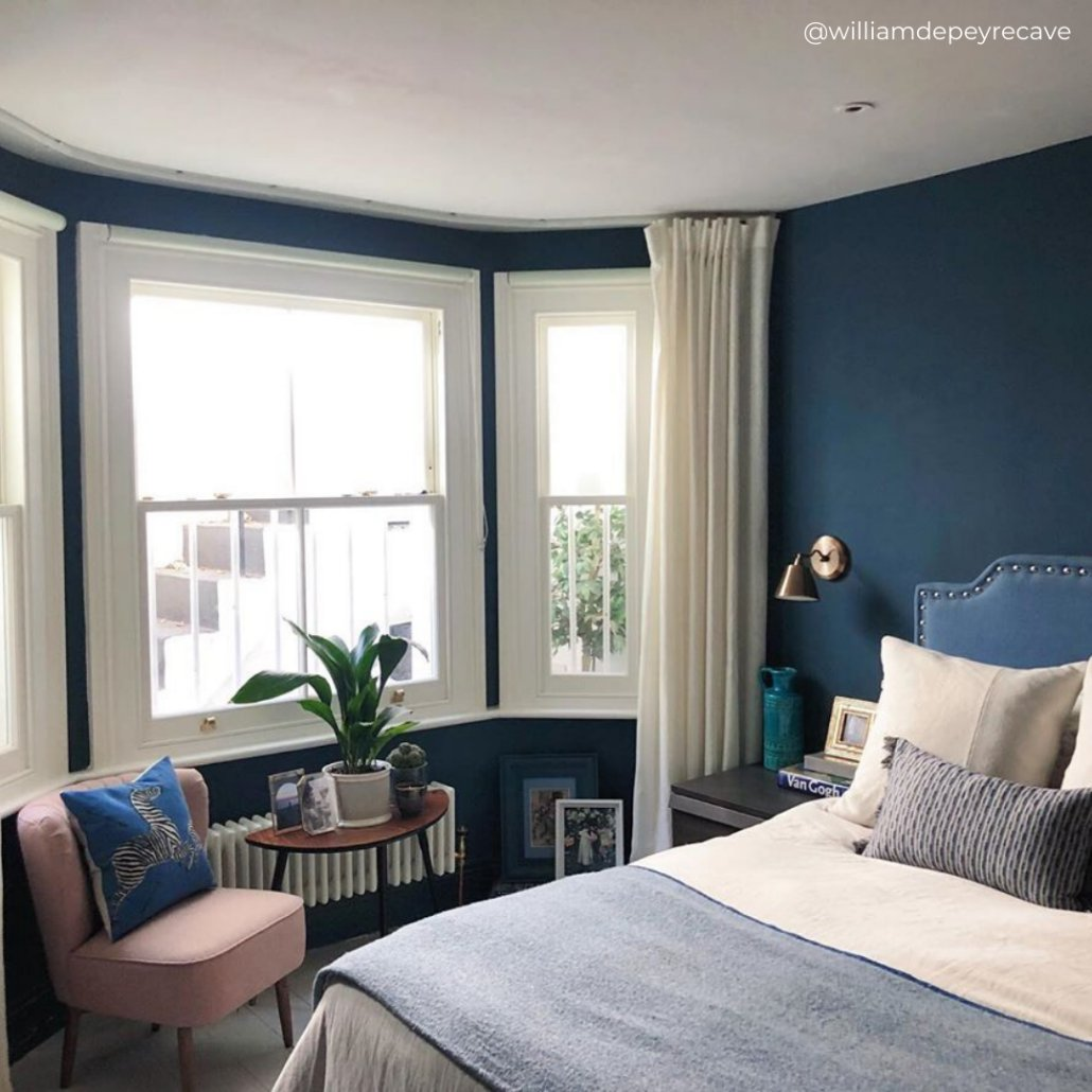 white low level radiator under a window in a blue bedroom