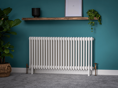 a white column radiator in a blue green room