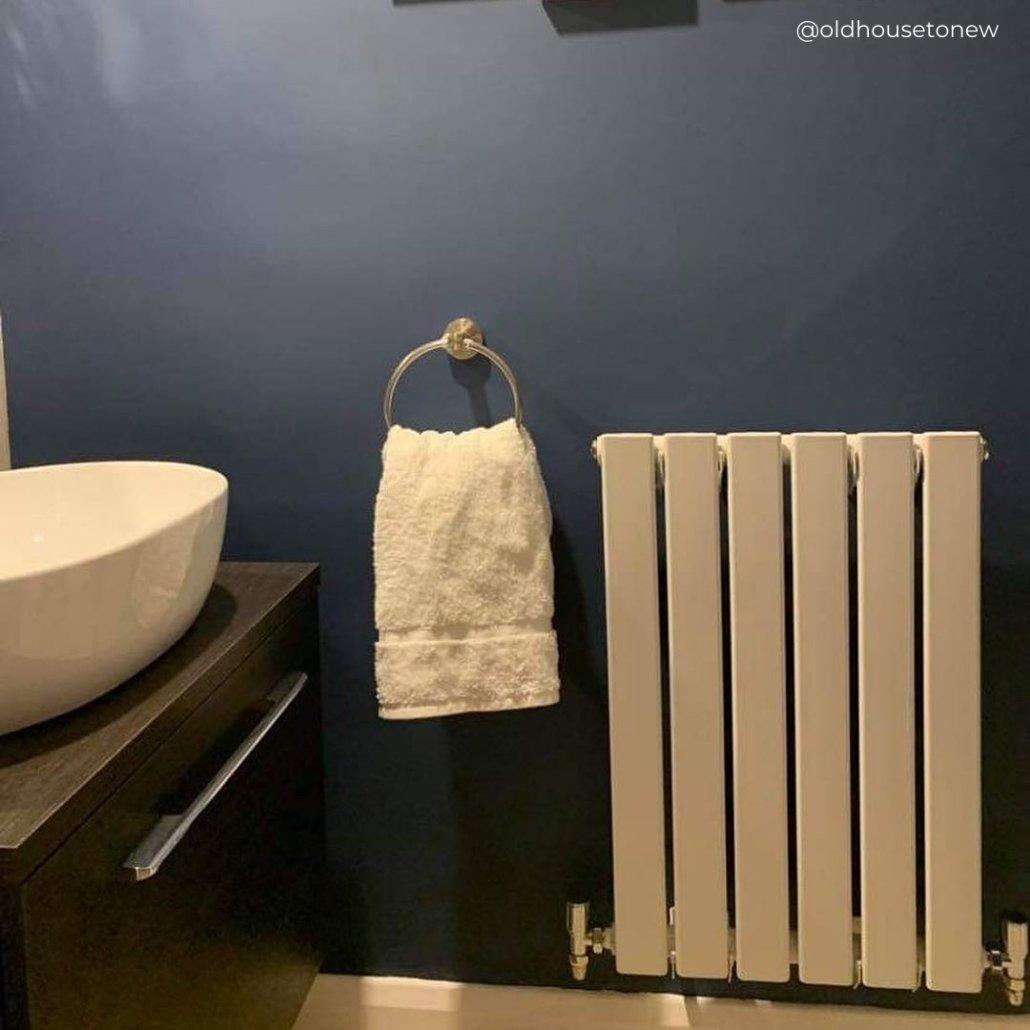 small radiator on a blue bathroom wall